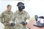 Staff Sgt. Daniel Butts, with the 386th Expeditionary Security Forces Squadron, trains with a SPECTRE Virtual Reality Trainer during a counter-unmanned aerial system (CUAS) course at Camp Buehring, Kuwait. Course instructor Chief Warrant Officer 2 Anthony Meneely stands behind him.