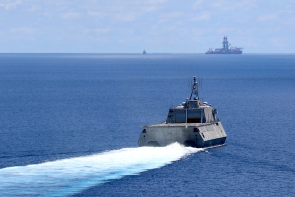 A littoral combat ship, seen from above, creates a white wake while traveling in vivid blue water.