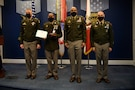 group of soldiers with awards standing on a stage.