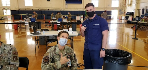 """Petty Officer Second Class, Andrew Simons, a health services technician (right), assists Air Force Maj. Katherine Rorer (left) at the Tripler Army Medical Center, Hawaii, during Tripler's MHS GENESIS """"go-live"""" mass vaccination evolution on Sept. 28. Simons recently participated in the Coast Guard's MHS GENESIS PACWAVE """"go-live"""" on Aug. 21 at Coast Guard Base Honolulu and was able to lend his electronic health records experience to the event."""