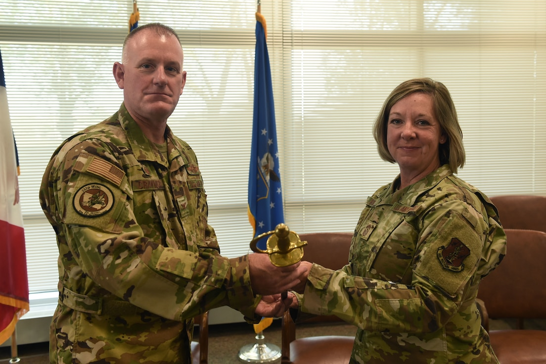 Col. Travis Crawmer (left) and Chief Master Sgt. Kris Rode (right) pose for a photo with the ceremonial chief's saber during the change of command ceremony held on September 19th, 2021 at the 132d Wing, Iowa Air National Guard, Des Moines, IA.