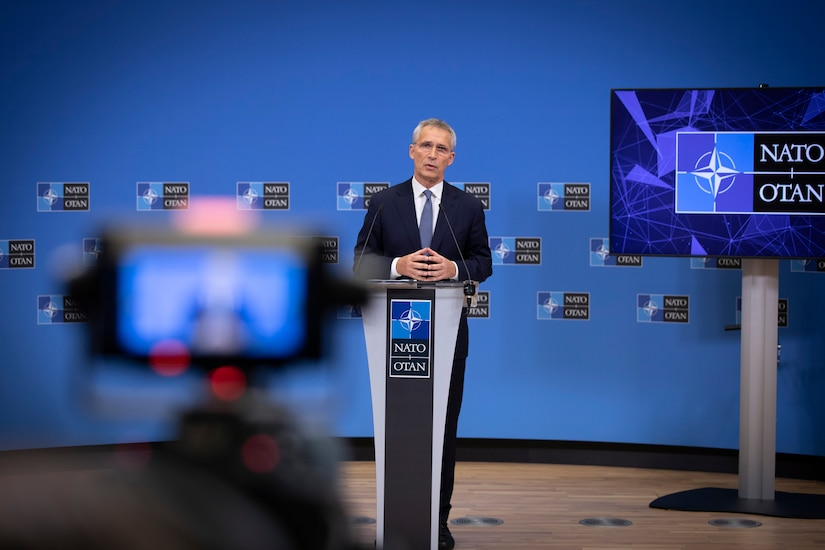 A man stands at a podium. Behind him is a backdrop with repeated NATO symbols. In the foreground, the same man is visible on a camera monitor.