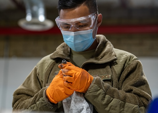 U.S. Air Force Senior Airman John Hizon, 56th Equipment Maintenance Squadron wheel and tire journeyman, inspects a bolt Oct. 14, 2021, at Luke Air Force Base, Arizona. The wheel and tire shop team demonstrated to 56th EMS leadership how they disassemble, clean, inspect, reassemble and store aircraft tires. The wheel and tire shop provides essential and reliable aircraft parts for the F-35A Lightning II and F-16 Fighting Falcon, supporting the world's greatest fighter pilots and combat-ready Airmen. (U.S. Air Force photo by Staff Sgt. Collette Brooks)