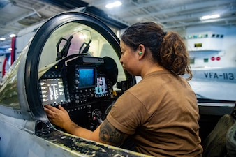 """Aviation Structural Mechanic 3rd Class Claudia Elantanez, a native of Anaheim, Calif. assigned to the """"Bounty Hunters"""" of Strike Fighter Squadron (VFA) 2, performs system checks on an F/A-18F Super Hornet in the hangar bay of Nimitz-class aircraft carrier USS Carl Vinson (CVN 70)."""