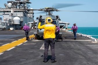 Aviation Boatswain's Mate (Handling) 3rd Class Zachary Janousek signals to an MH-60S Sea Hawk helicopter attached to Helicopter Sea Combat Squadron 21 on the flight deck of the amphibious assault ship USS Essex (LHD 2) during flight operations.