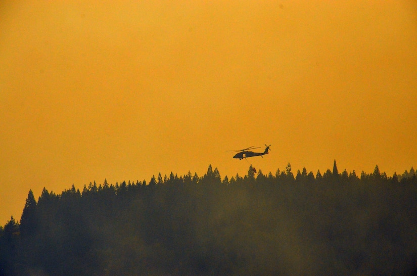 A helicopter carrying a bambi bucket flies over a treeline. The sky is orange due to smoke from forest fires.