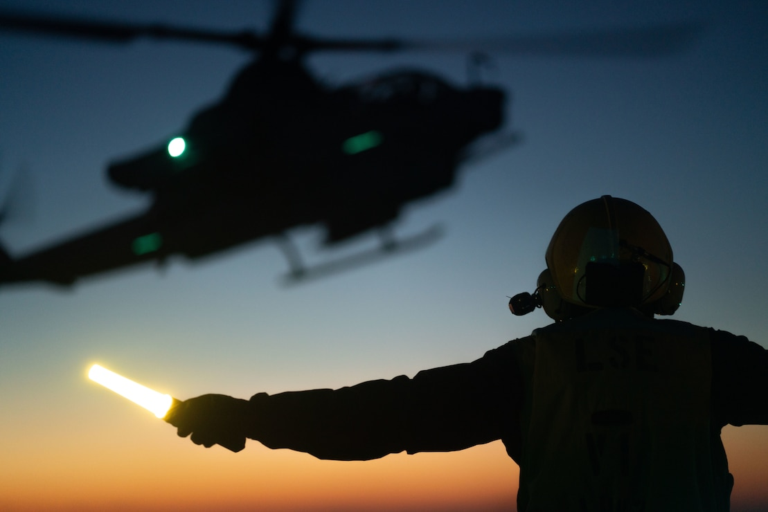 U.S. Navy Aviation Boatswains Mate Handling 3rd Class Israel Avalos, assigned to amphibious assault ship USS Kearsarge (LHD 3), signals an AH-1 Cobra for landing during flight operations, Oct. 20. The 22nd MEU and Amphibious Squadron Six is underway for PHIBRON-MEU Integrated Training in preparation for an upcoming deployment. PMINT is the first at-sea period in the MEU's Predeployment Training Program; it aims to increase interoperability and build relationships between Marines and Sailors.