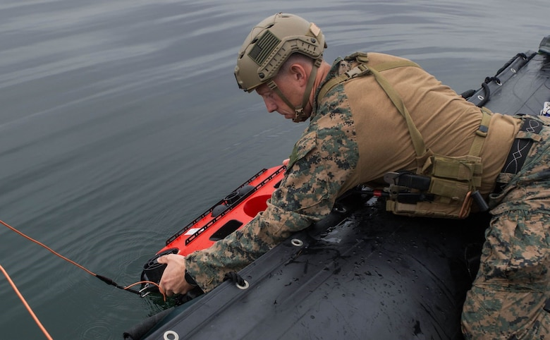 Staff Sgt. Seth Barnes, an explosive ordnance disposal technician from Littoral Explosive Ordnance Neutralization Platoon, 7th Engineer Support Battalion, 1st Marine Logistics Group, releases the Remotely Operated Vehicle into the water during a demonstration in San Diego, Calif., Oct. 6, 2021. The ROV asset aids the Marine Corps in naval force integration by giving Marines the capabilities to work alongside Navy EOD.