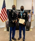 Two men standing in Army Service Uniform, receiving an award.