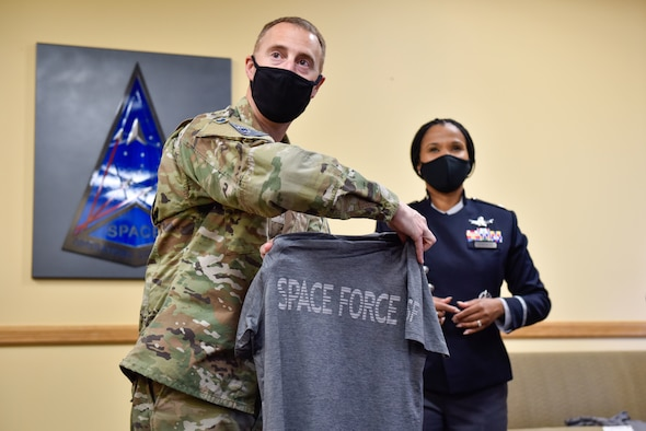 U.S. Space Force Col. Matthew Cantore and Lt. Col. Alison Gonzalez, both from the Office of the Chief of Space Operations, reveal a prototype of the new USSF physical training uniform to members of Space Delta 4's geographically-separated units over Zoom on Buckley Space Force Base, Colo., Oct 20, 2021. The prototypes are being shown to Guardians around the force to ensure maximum satisfaction with the finished product. (U.S Space Force photo by Airman 1st Class Wyatt Stabler)