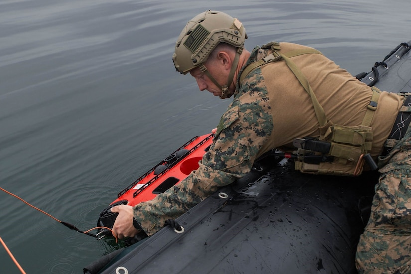 A Marine places a device into the water.