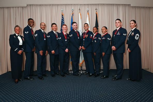 Airman Leadership School Class 21H graduates stand for a photo, flanked by Col. Katrina Stephens, left, installation commander, and Chief Master Sgt. Holly Burke, acting installation command chief, during an ALS graduation at Hanscom Air Force Base, Mass., Oct. 21. The graduates will go on to serve their units as first-line supervisors. (U.S. Air Force photo by Todd Maki)