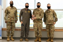 Captain Robert Moran, 2nd Operational Support Squadron B-52 weapon systems officer, and Tech. Sgt. Julio Torres, non-commissioned officer of quality assurance, stand between Brig. Gen. Kenyon Bell, director, Logistics and Engineering, Air Force Global Strike Command, and Chief Master Sgt. Charles Hoffman, AFGSC command chief, with his trophy at STRIKEWERX Spark Sprint competition Friday, Oct. 15.