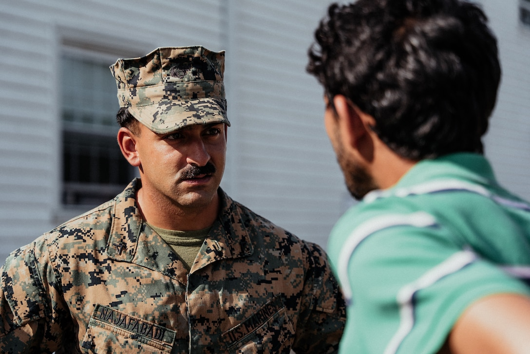 U.S. Marine Corps Lance Cpl. Nima H. Najafabadi, a machine gunner with 3rd Battalion, 6th Marine Regiment, speaks with an Afghan individual on Fort Pickett, Virginia, Oct. 13, 2021. Najafabadi, originally from Shiraz, Iran, came to the United States when he was 8 years old. Now, he is grateful for the opportunity to help families who are in a similar position that he was in 20 years ago. The Department of Defense, through U.S. Northern Command, and in support of the Department of Homeland Security, is providing transportation, temporary housing, medical screening, and general support for at least 50,000 Afghan evacuees at suitable facilities, in permanent or temporary structures, as quickly as possible. This initiative provides Afghan personnel essential support at secure locations outside Afghanistan. (U.S. Marine Corps photo by Sgt. Corey Mathews)