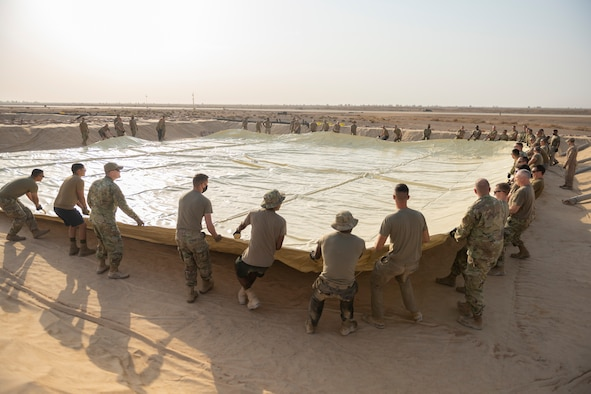 U.S. Airmen with the 332nd Air Expeditionary Wing spread out a collapsible fabric tank