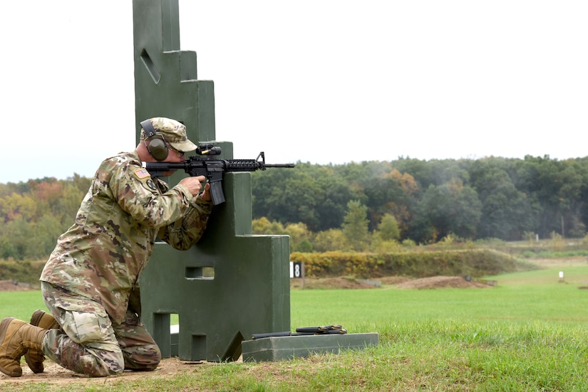 A soldier kneels behind an obstacle while firing at a target.