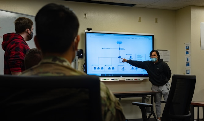 Samuel Gerard, University of Nevada, Reno (UNR) Cyber Club member and Nevada Cyber Range (NCR) developer, briefs members of the 152nd Communications Flight (CF), Nevada Air National Guard, on the technical layout of the NCR at the University of Nevada, Reno, Oct. 15, 2021. The 152nd CF and UNR's Cyber Club have created a training partnership to develop both organizations' cybersecurity skills.