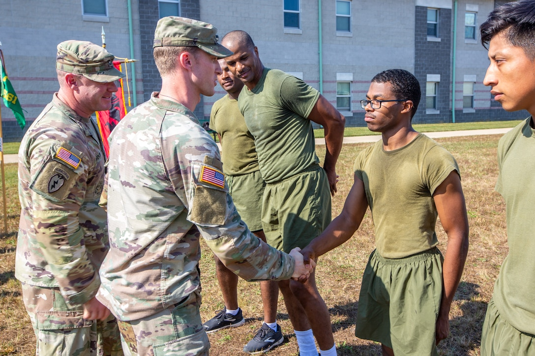 U.S. Army Capt. Joshua Love, company commander for 561st Military Police Company, 716th Military Police Battalion, 16th Military Police Brigade, 101st Airborne Division, gives a challenge coin to Lance Cpl. Javon Carpio, an engineer equipment operator assigned to Marine Wing Support Squadron 273, in Fort Pickett, Virginia, Oct. 22, 2021.