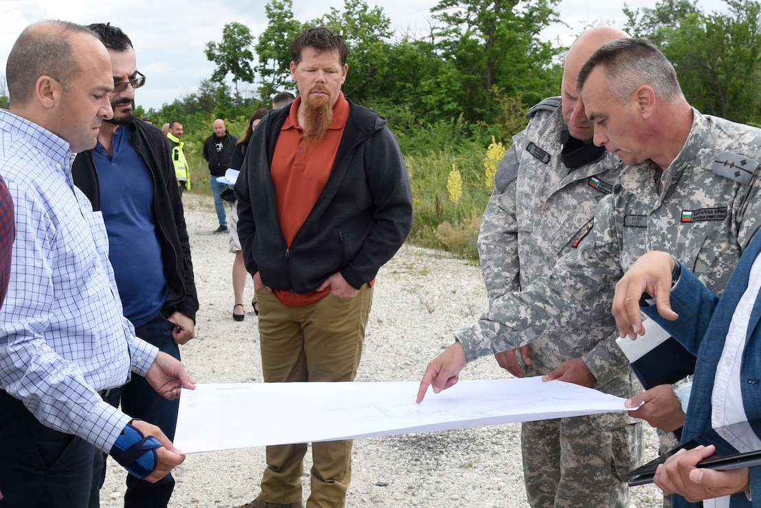 U.S. Army Corps of Engineers, Europe District Southern Europe Area Engineer Bryce Jones, left, provides an overview of ongoing and upcoming construction projects to members of the Bulgarian Air Force at Graf Ignatievo Air Base in Bulgaria June 16, 2021. Jones was recognized as the U.S. Army Corps of Engineers Administrative Contracting Officer of the Year during a virtual ceremony October 25, 2021 for his work in support of the U.S. Army Corps of Engineers missions in Bulgaria as well as several other Southern European countries. (U.S. Army photo by Alfredo Barraza)