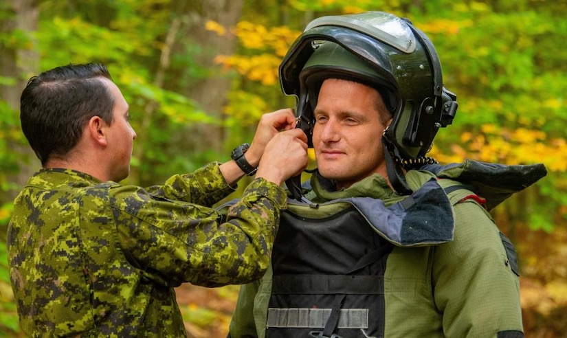 A soldier works on the helmet straps of another soldier.