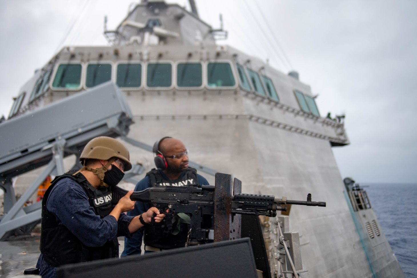 Lt. Iman Amaya, from Orange Park, Fla., left, fires a M240D machine gun aboard Independence-variant littoral combat ship USS Charleston (LCS 18), during a live fire exercise.