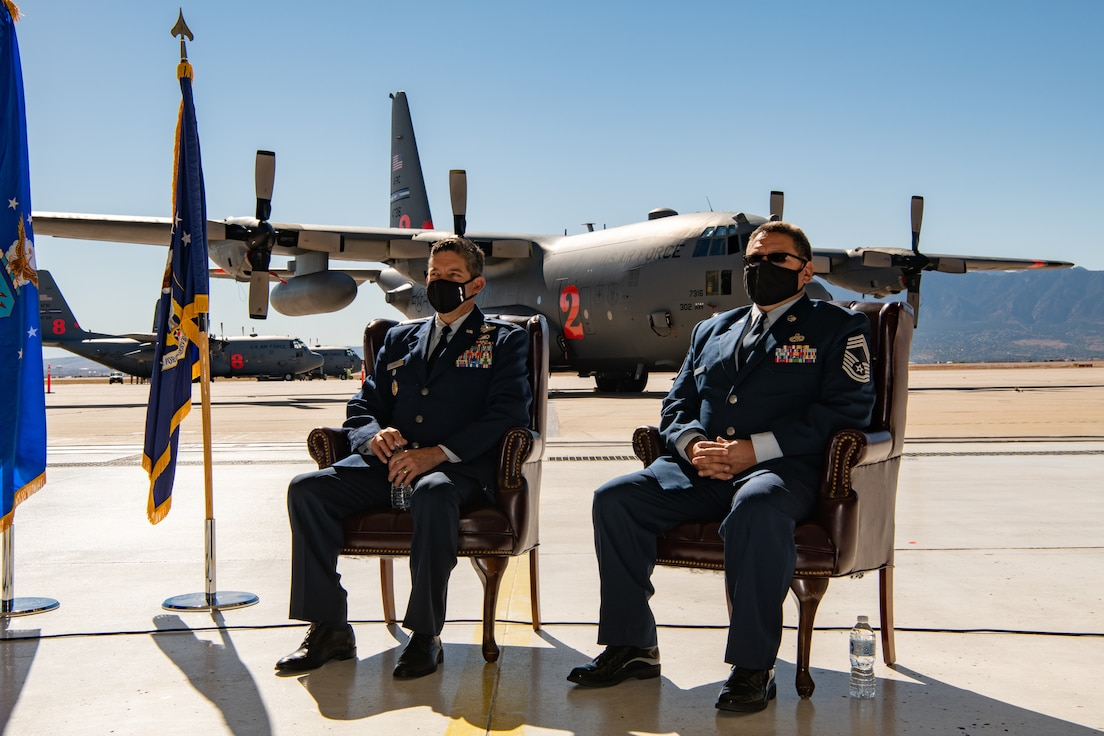 Two men in service dress sit in chairs with a C-130 on a parking ramp behind them.