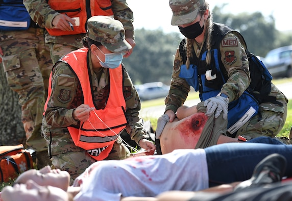 """U.S. Air Force 1st Lt. Lucia Moreno, 81st Operational Medical Readiness Squadron medical flight nurse, and Airman Kaylee Exum, 81st OMRS medical technician, provides medical assistance to a """"victim"""" during an active shooter exercise outside the Taylor Logistics Center at Keesler Air Force Base, Mississippi, Oct. 21, 2021. The scenario included an active duty Air Force member who simulated open fire in order to test the base's ability to respond to and recover from a mass casualty event. (U.S. Air Force photo by Kemberly Groue)"""