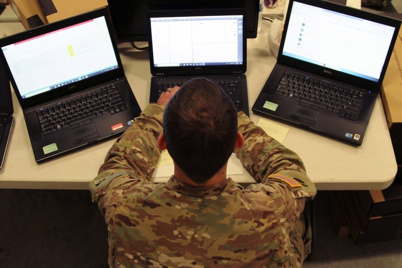 A soldier works on three laptop computers.