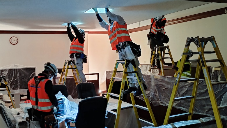 contractors install energy efficient fixtures and light bulbs in an office