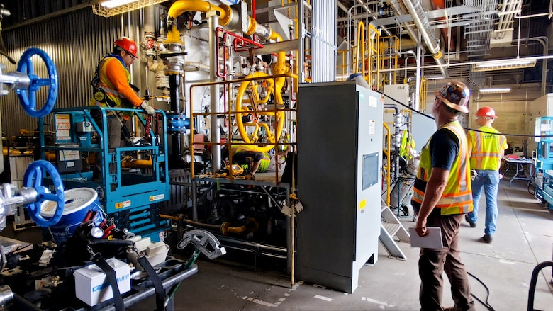 Contractors work on a natural gas-powered steam plant