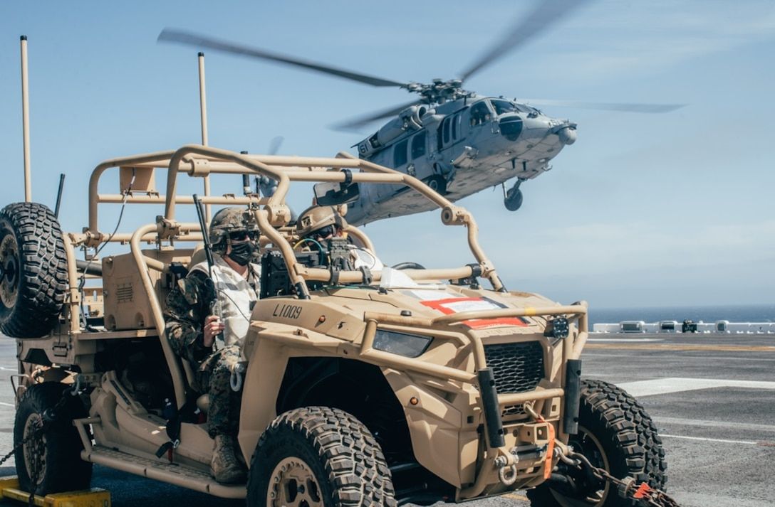 U.S. Marine Corps Sgt. Tyler Roup, left, a team leader, and Cpl. Connor Reddy, a section leader, both with Marine Medium Tiltrotor Squadron 65, 11th Marine Expeditionary Unit, sit in a Light Marine Air Defense Integrated System and watch for unmanned aerial systems while an MH-60S Sea Hawk with Helicopter Sea Combat Squadron 21 takes off from the flight deck of the amphibious assault ship USS Essex during a simulated strait transit, March 29. U.S. Navy and Marine Corps integration training provides the Essex Amphibious Ready Group/11th MEU its first opportunity to plan, brief, and execute multiple mission packages. Essex is underway conducting routine operations in U.S. Third Fleet.