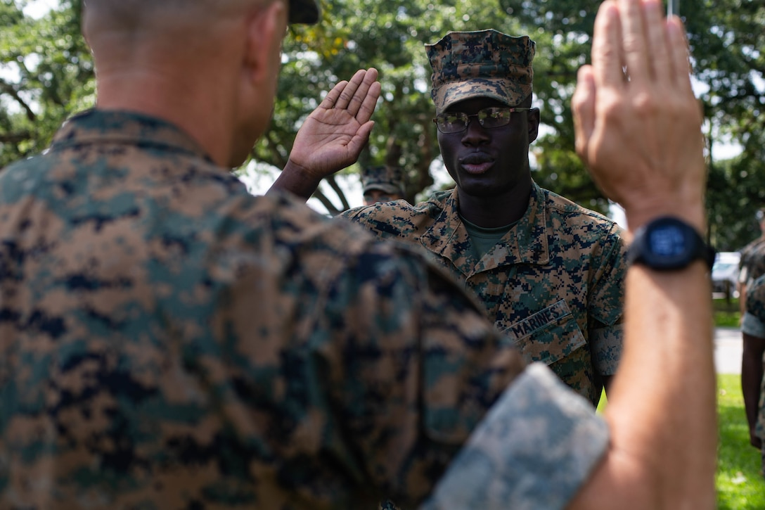 U.S. Marine Corps Lance Cpl. Anthonas Thermidor, a legal services specialist with Headquarters Battalion, 2d Marine Division, recites the oath of enlistment during a flag presentation ceremony at Camp Lejeune, N.C., Aug. 27, 2021. Thermidor, a Haitian native, received an American flag to commemorate earning American citizenship. (U.S. Marine Corps photo by Lance Cpl. Reine Whitaker)