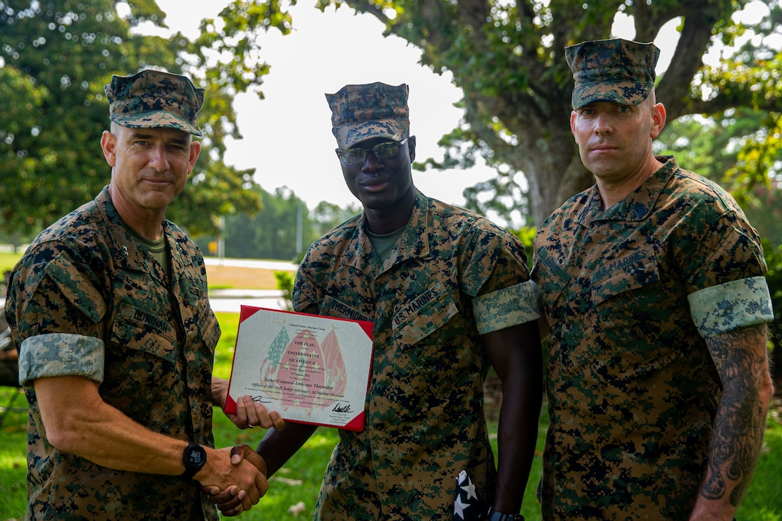 U.S. Marine Corps Maj. Gen. Francis Donovan, left, commanding general, Lance Cpl. Anthonas Thermidor, center, a legal services specialist with Headquarters Battalion, and Sgt. Maj. Daniel Krause, right, sergeant major, all with 2d Marine Division, pose for a photo after a flag presentation ceremony at Camp Lejeune, N.C., Aug. 27, 2021. Thermidor, a Haitian native, received an American flag to commemorate earning American citizenship. (U.S. Marine Corps photo by Lance Cpl. Eric Rodriguez)