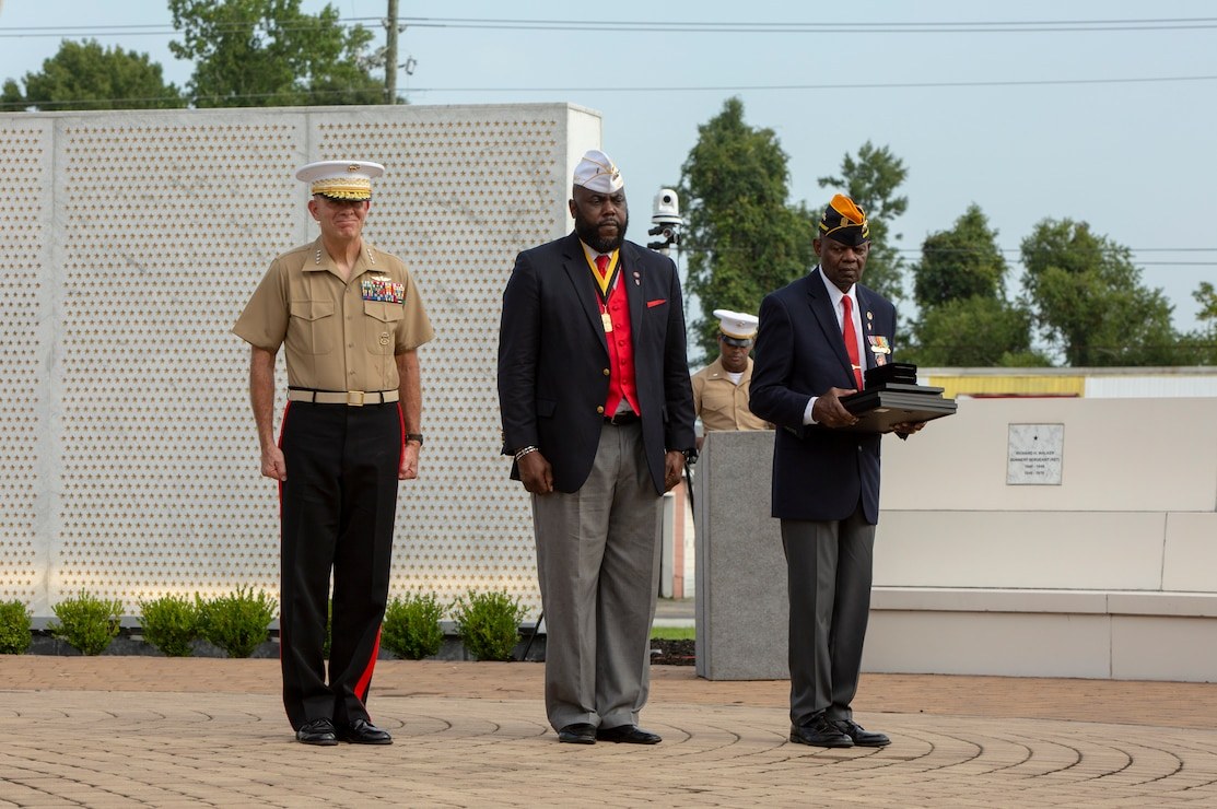U.S. Marine Corps Commandant Gen. David H. Berger, left, James T. Averhart Jr., center, National President of the Montford Point Marine Association and Johnny B. Young Jr., right, president of the Chapter 10 Montford Point Marine Association stand at attention during the 12th annual Montford Point Marine Day Ceremony at the Lejeune Memorial gardens, Jacksonville, North Carolina, Aug. 26, 2021.