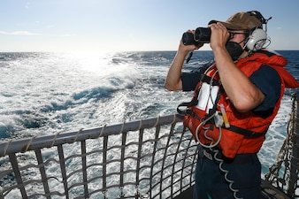 Seaman Brayden Norton, from Howe, Oklahoma, stands an aft lookout watch on the flight deck aboard the guided-missile destroyer USS Forrest Sherman (DDG 98).