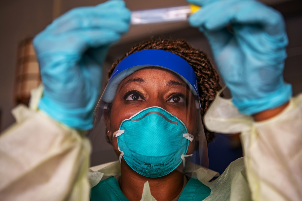 An airman wearing a face mask, gloves and medical gown holds up a test swab to check the label.