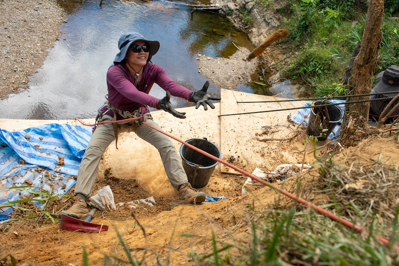 U.S. Space Force Master Sgt. Hanh Le, a Defense POW/MIA Accounting Agency recovery team linguist, prepares to catch a bucket during a recovery mission in Quang Nam Province, Vietnam, June 29, 2021. DPAA's mission is to achieve the fullest possible accounting for missing and unaccounted-for U.S. personnel to their families and our nation. (U.S. Air Force photo by Staff Sgt. Jonathan McElderry)