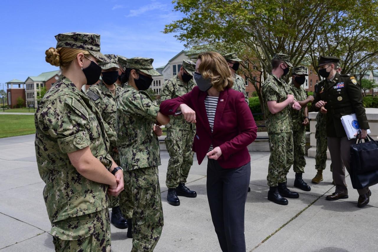A woman greets sailors.