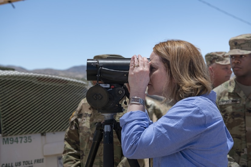 A woman uses a device to view something in the distance. A service member stands next to her.