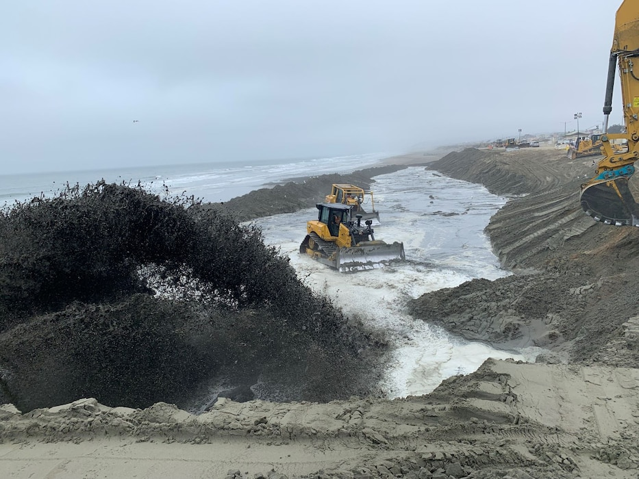 Mounds of sand on a beach with construction equipment.