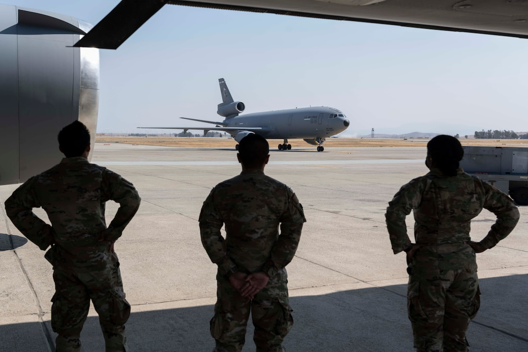 Three Airmen watch a plane taxi on the flight line