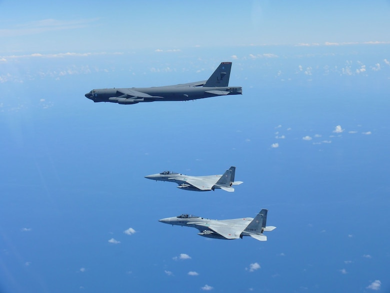 Two Japan Air Self-Defense Force (JASDF) F-15's escort a U.S. Air Force B-52 Stratofortress August 31, 2021 over the Indo-Pacific region. The JASDF and the U.S. Air Force conducted bilateral training to enhance deterrence and response capabilities. (Photo by Japan Air Self-Defense Force)