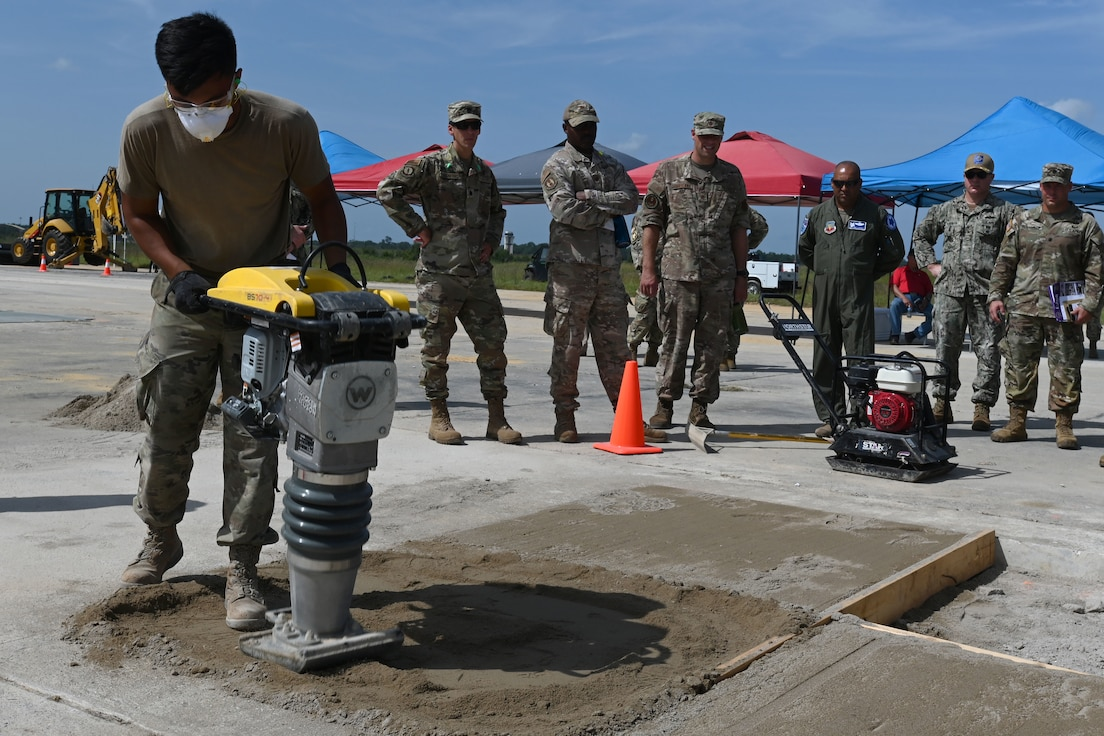 U.S. Air Force civil engineers from the pavements and construction equipment career field, from eight separate units, team up with U.S. Navy Seabees from the Naval Mobile Construction Battalion 133, Gulfport, Mississippi for an Expedient and Expeditionary Airfield Damage Repair (E-ADR) distinguished visitors' demonstration at McEntire Joint National Guard Base, South Carolina, Aug. 31, 2021. The purpose of the training is to provide just enough, just in time repair capability with minimal cost and materials in a wartime situation.  (U.S. Air National Guard photo by Senior Master Sgt. Edward Snyder, 169th Fighter Wing Public Affairs)