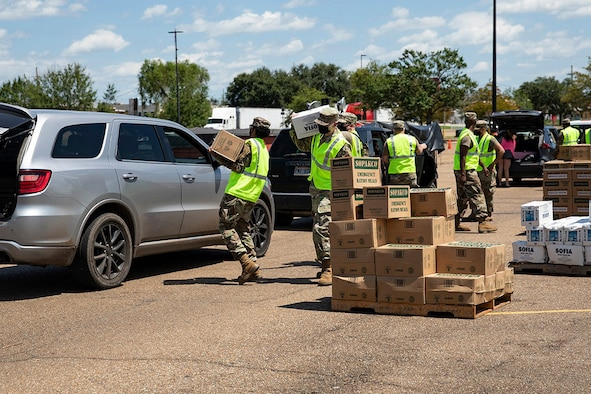 Members of the Louisiana National Guard distribute meals ready to eat at one of nine distribution points set up across three parishes to aid in the recovery from Hurricane Ida.