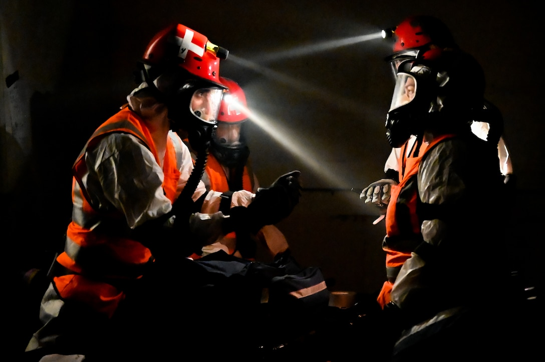 Airmen from the 155th Chemical Biological Radiological Nuclear Enhanced Response Force Package search and extraction team discuss patients found in a building collapse exercise, Aug. 17, 2021, in Lincoln, Neb.