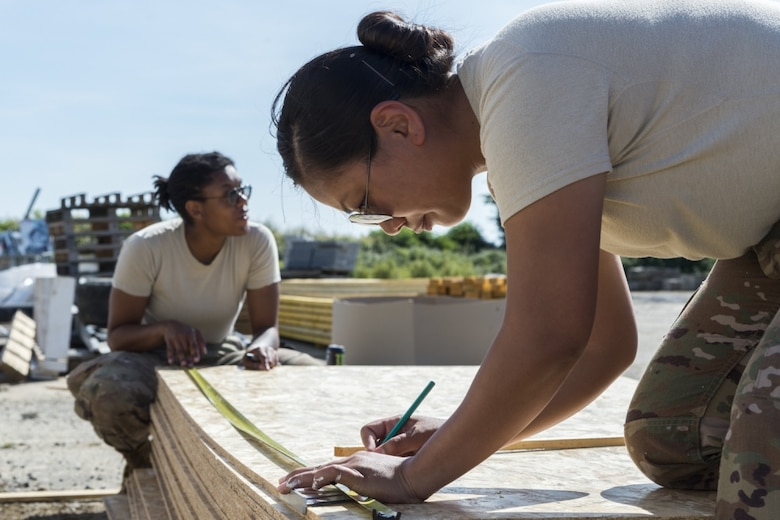 Two female Airmen work on engineering projects. A Women's Initiatives Team is one of eight Barrier Analysis Working Groups under the Air Force Materiel Command Major Command Barrier Analysis Working Group umbrella, which was created as part of ongoing efforts to drive greater diversity and inclusion across the enterprise.