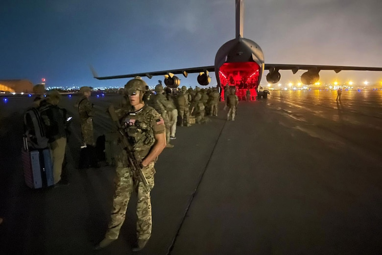 A soldier stands with a weapon a flightline as others stand in line by an open aircraft.