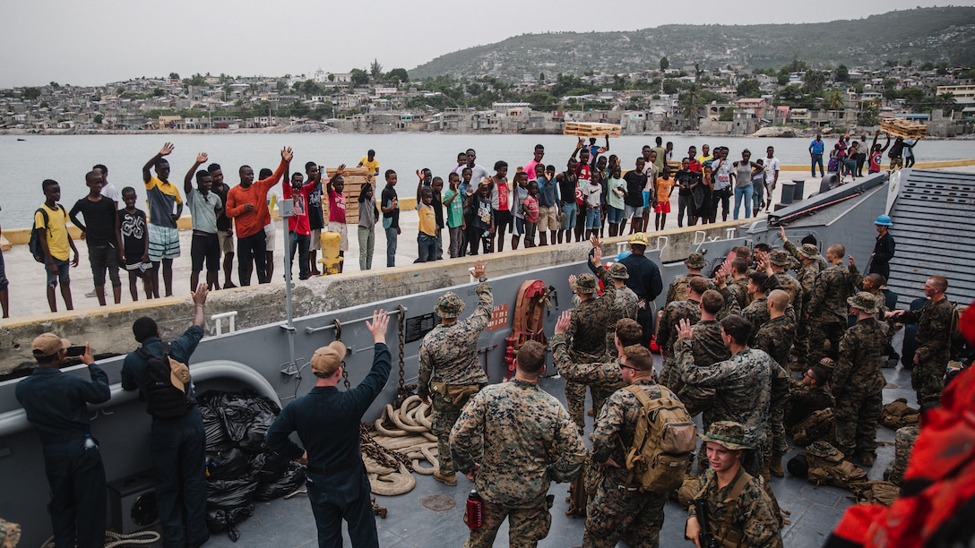 U.S. Marines and Sailors with Joint Task Force-Haiti (JTF-Haiti) wave to locals after helping offload boxes for redistribution in Port of Jeremie, Haiti, Aug. 31, 2021. The Marines and sailors aboard the USS Arlington (LPD 24) have been working in support of JTF-Haiti for a humanitarian assistance and disaster relief mission. (U.S. Marine Corps photo by Lance Cpl. Jacqueline C. Arre)