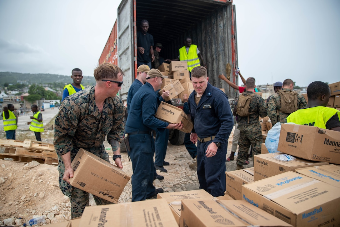 U.S. Marines and Sailors with Joint Task Force-Haiti (JTF-Haiti) and volunteers help offload boxes for redistribution in Port of Jeremie, Haiti, Aug. 31, 2021.