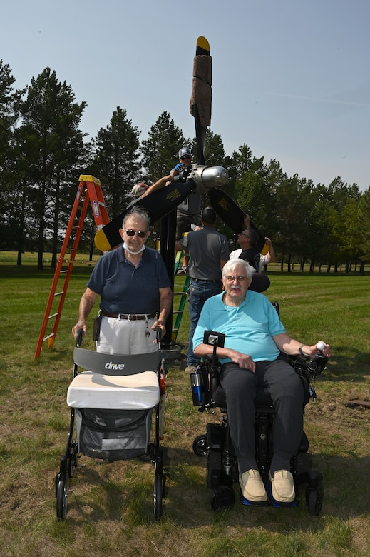 Two elderly men pose for a photo in front a U.S. Air Force B-25 propeller display being installed by four men on the grassy grounds of the North Dakota Veterans Home, Lisbon, N.D., Sept. 1, 2021.